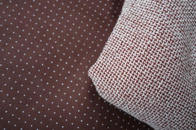Dünner brauner Baumwolltoff mit Punkten und grob gewebte Wollte